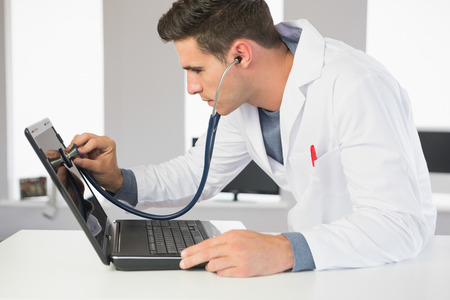 computer hardware: Attractive focused computer engineer examining laptop with stethoscope in bright office