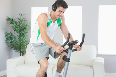 Sporty handsome man training on exercise bike listening to music in bright living room photo