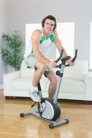 Cheerful handsome man training on exercise bike listening to music in bright living room photo