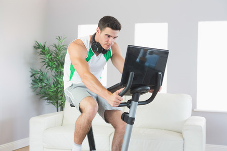 Stern handsome man training on exercise bike using laptop in bright living room photo