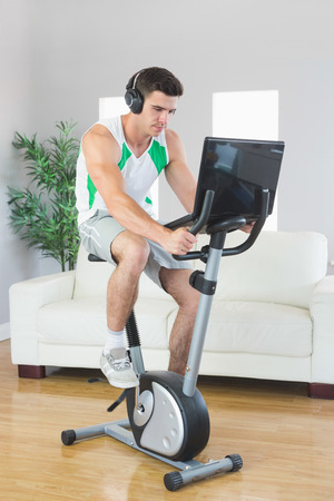 Serious handsome man training on exercise bike using laptop in bright living room photo