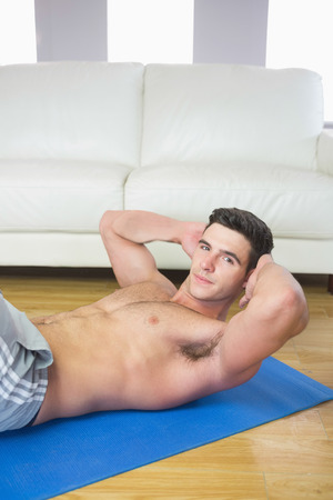 Content handsome man doing sit ups in bright living room photo