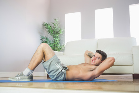 Sexy handsome man doing sit ups in bright living room photo