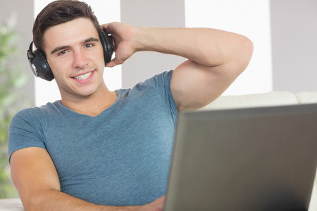 Cheerful handsome man using laptop listening to music in bright living room photo