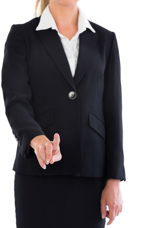 Mid section of blonde businesswoman pointing at camera on white screen photo
