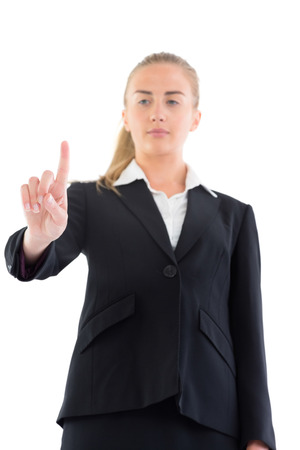 Low angle view of young businesswoman pointing on white background photo