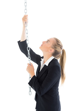 Profile view of ponytailed blonde woman pulling a chain on white background photo