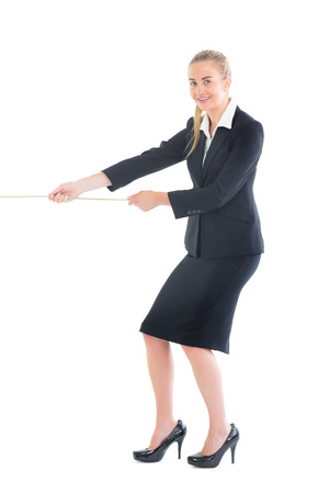 Cheerful blonde businesswoman pulling a rope on white background photo