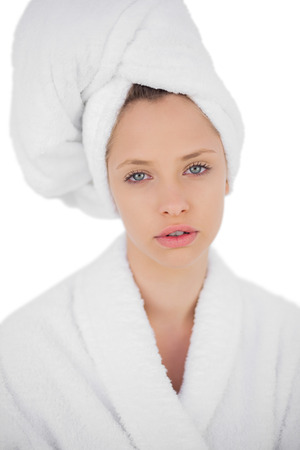 Thinking brunette in bathrobe looking at camera on white background photo