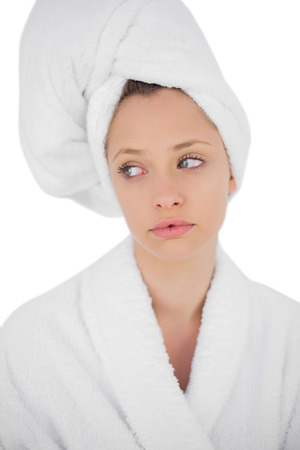 Thinking brunette in bathrobe looking away on white background photo