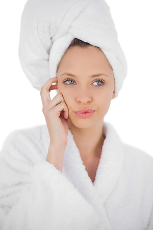 Content brunette in bathrobe looking away on white background photo