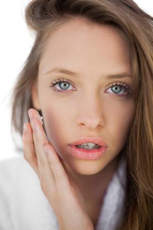 Pensive brunette in bathrobe rubbing her cheek with cream on white background photo