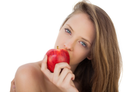 Pensive brunette model eating an apple on white background photo