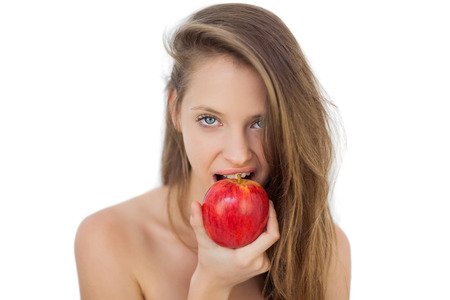 Pretty brunette model eating an apple on white background photo