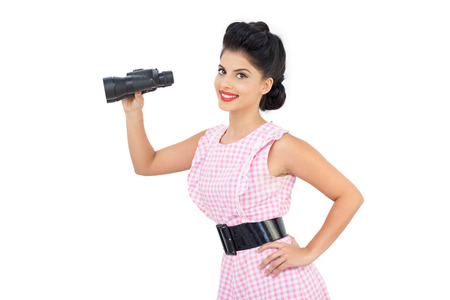 Smiling black hair model holding binoculars on white background photo
