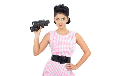 Pleased black hair model holding binoculars on white background photo