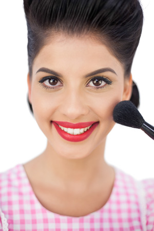 Smiling black hair model applying powder on her cheek on white background photo