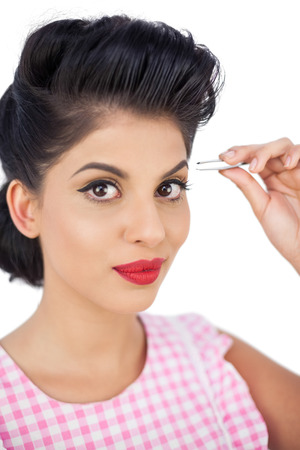 Gorgeous black hair model using a tweezer on white background photo