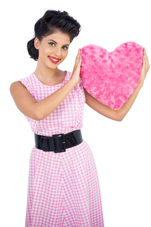 Playful black hair model holding a pink heart shaped pillow on white background photo