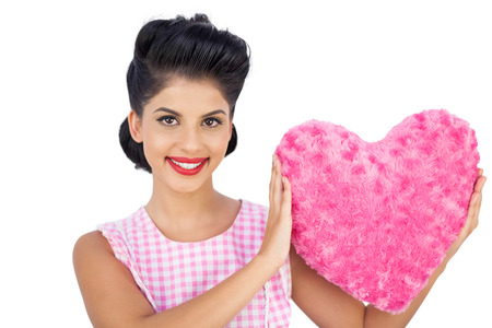 Lovely black hair model holding a pink heart shaped pillow on white background photo