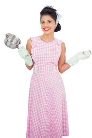 Joyful black hair model holding a pan and wearing rubber gloves on white background  photo