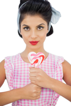 Charming black hair model holding a heart shaped lollipop on white background photo