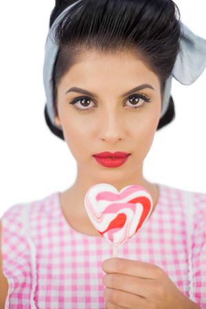 Serious black hair model holding a heart shaped lollipop on white background photo