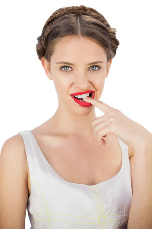 Seductive model in white dress posing with a finger in her mouth on white background photo
