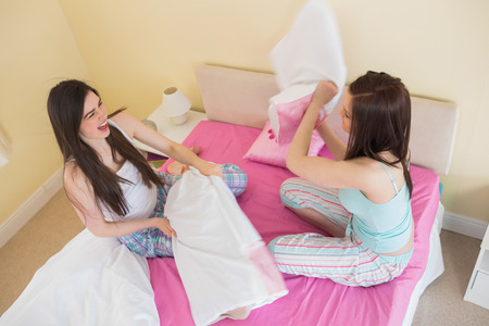 Pillow fight: Happy friends in pajamas having a pillow fight on bed in bedroom at home