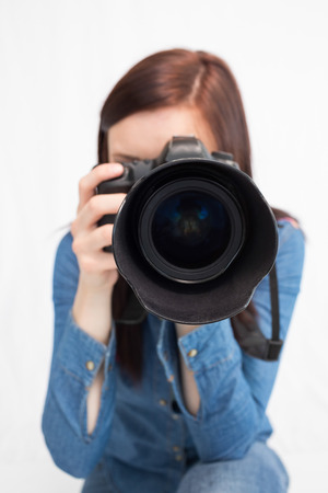 Casual young photographer against white background taking picture of camera photo