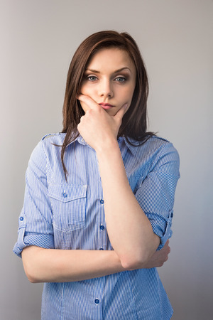 Thoughtful serious brunette posing on grey background photo