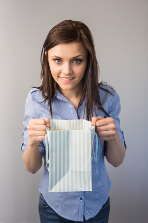 Cheerful pretty brunette on grey background receiving a present photo