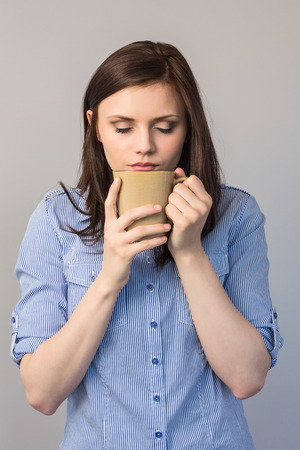 Young pretty brunette on grey background smelling coffee photo