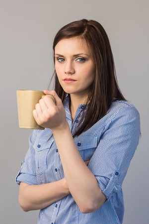 Serious pretty brunette on grey background holding cup of coffee photo