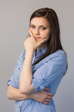 Pensive pretty brunette posing on grey background photo