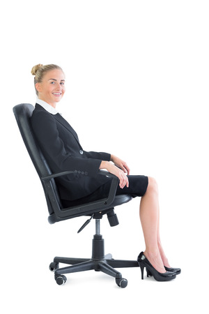 Attractive businesswoman sitting on an office chair smiling at camera photo