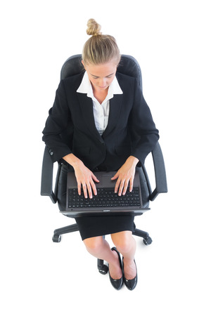 Focused young businesswoman using her notebook sitting on an office chair photo