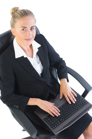 Young businesswoman sitting on her office chair using her notebook looking at camera photo