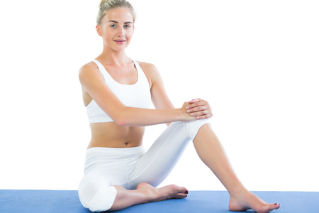 Toned smiling blonde sitting on exercise mat on white background photo