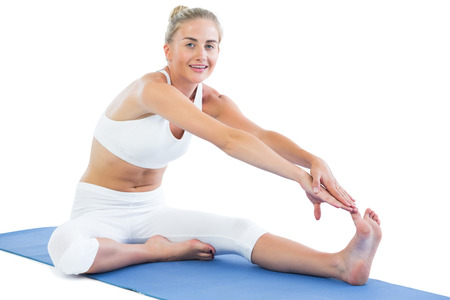 Toned smiling blonde sitting on exercise mat stretching right leg on white background photo