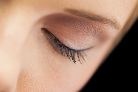 eye liner: Close up on eye wearing eye liner and natural eye shadow on black background