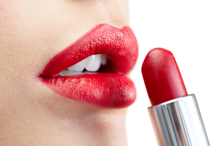 Extreme close up on model on white background applying red lipstick photo