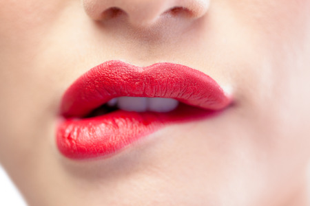Close up on sensual model biting red lips on white background Stock Photo