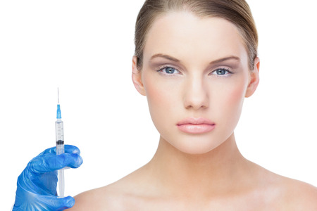surgical needle: Serious beautiful blonde on white background holding surgical needle Stock Photo