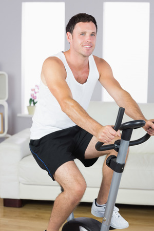 Smiling sporty man exercising on bike in bright living room photo