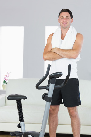 cross armed: Smiling sporty man standing next to exercise bike cross armed in bright living room