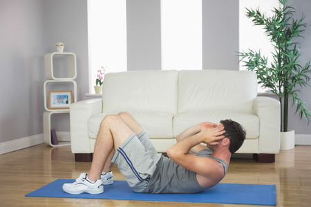 sit ups: Handsome sporty man doing sit ups in bright living room Stock Photo