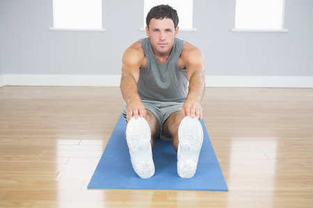 touching toes: Attractive sporty man stretching his legs in bright room