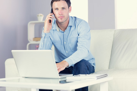 Content casual man using laptop and phoning in bright living room photo