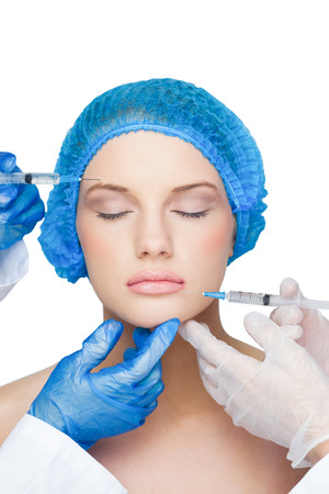 surgical cap: Surgeons making injection on peaceful blonde wearing blue surgical cap on white background Stock Photo